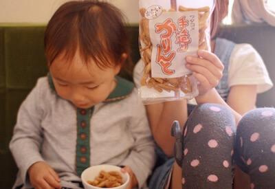 ワダコメのかりんとうを食べる子供