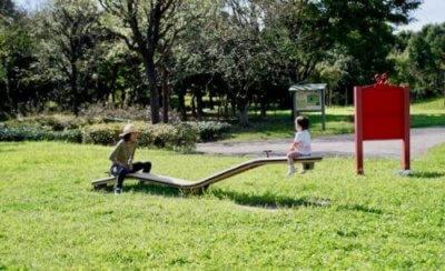 日当たりの良い公園でシーソーする親子