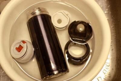 過炭酸ナトリウムを溶かした容器に水筒を付けた画像