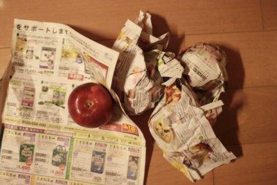 りんごを1個ずつ新聞紙で包む