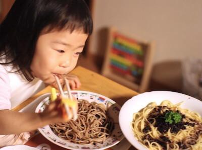 黒米を使ったパスタを食べている娘