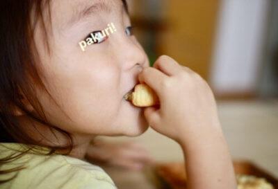 米粉ケーキを頬張る子ども